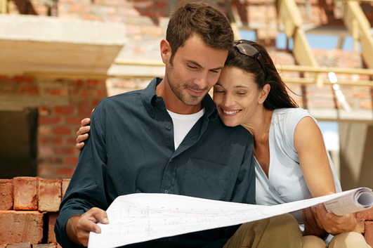 Couple with blueprints at a construction site